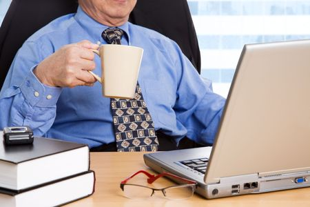 A shot of a mature businessman holding a coffee cup working on his laptop in the office photo