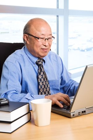 A shot of a senior asian businessman working on his laptop at the office photo
