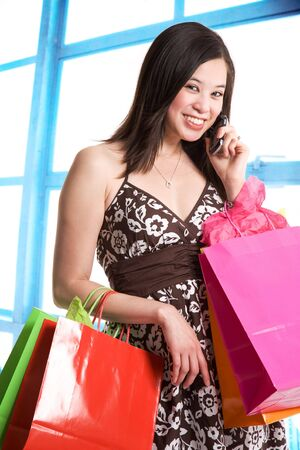 A shot of a beautiful asian woman carrying shopping bags and talking on the phone in a store photo