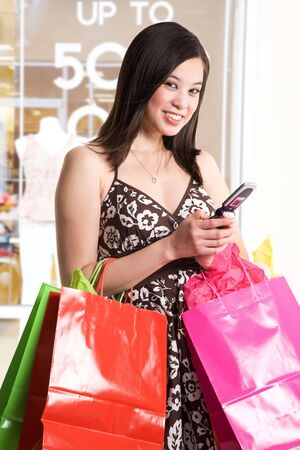 shopper: A shot of a beautiful asian woman carrying shopping bags and texting on her cell phone in a store Stock Photo