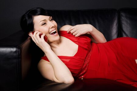 woman on couch: A shot of a happy and beautiful young woman lying down on the couch talking on the cellphone Stock Photo
