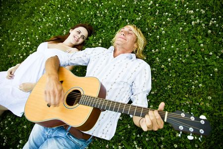 A shot of a caucasian couple lying down on the grass playing guitar and enjoying the outdoor photo