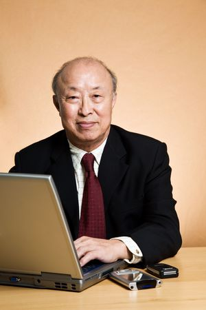 senior business: A shot of a mature asian businessman working on his laptop