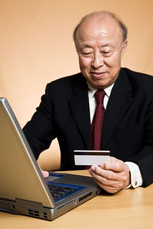 A shot of a senior asian businessman holding a credit card ready to make an online purchase (focus on the credit card) photo
