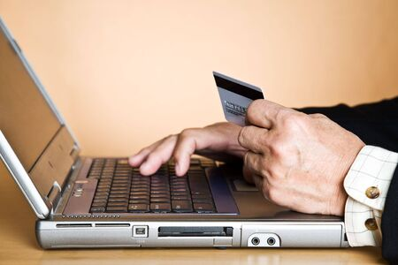 online: A shot of a senior asian businessman holding a credit card getting ready to buy online
