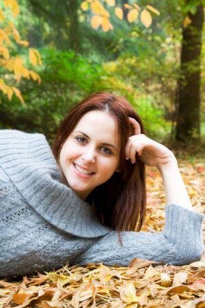 A portrait of a beautiful young caucasian girl lying on the ground in fall season Stock Photo - 3361918