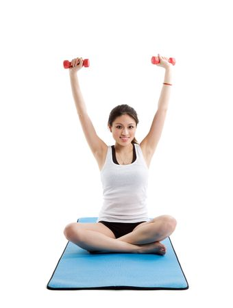 An isolated shot of a beautiful asian woman sitting on a yoga mat lifting dumbbells photo