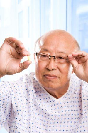 A shot of an elderly asian man examining his pill photo
