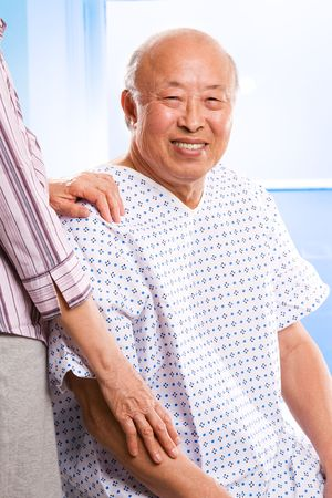A shot of a happy senior asian male accompanied by his wife in the hospital photo