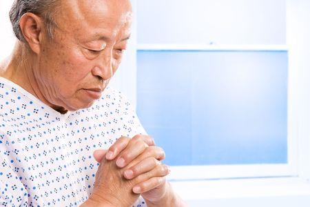 A shot of a senior asian man praying in hospital