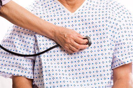 Een schot van een senior patiënt wordt gecontroleerd met een stethoscoop