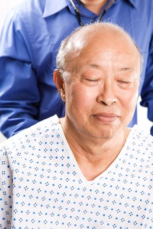 An isolated shot of a doctor examining a senior asian man photo