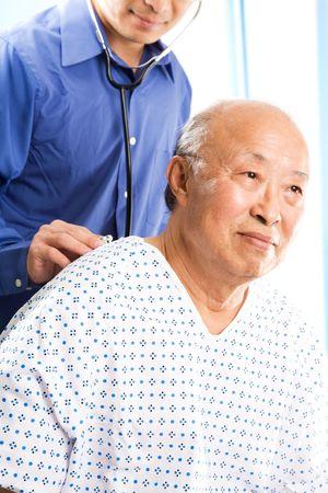 Een shot van een arts de behandeling van een hoge asian patiënt in een ziekenhuis Stockfoto