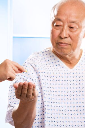 A shot of a senior asian man receiving a pill from a nurse photo
