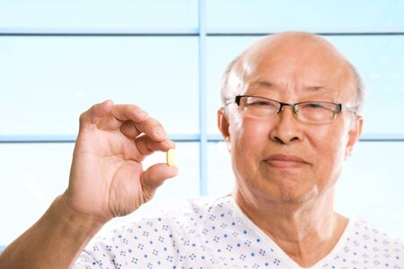 A shot of a senior asian man holding a pill photo