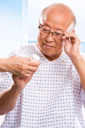 A shot of an elderly asian man examining his prescription photo