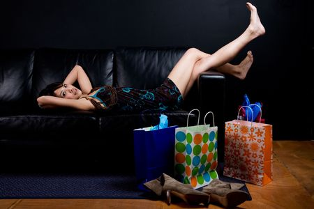 A shot of a beautiful asian woman resting on the couch after shopping photo