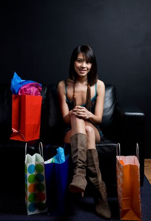 A shot of a beautiful asian woman sitting on a couch with shopping bags photo