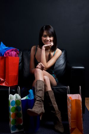 A shot of a beautiful asian woman sitting on the couch with shopping bags photo