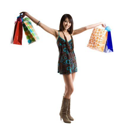 spender: An isolated shot of a beautiful asian woman carrying shopping bags