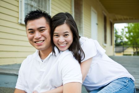 A shot of a beautiful young couple sitting on the porch of their  photo