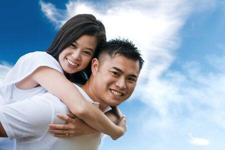 Een shot van een Aziatische paar buitenshuis doet piggback rit