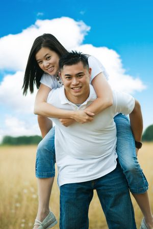 happy asian couple: A happy asian couple doing piggyback ride outdoor in a park