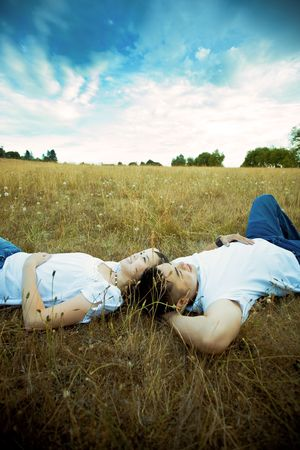 A shot of an asian couple in love lying down on grass under the blue sky photo