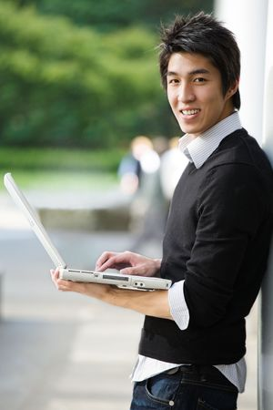 A shot of an asian student working on his laptop at the campus photo