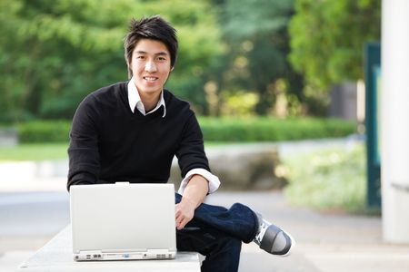 laptop outside: A shot of an asian student studying on his laptop