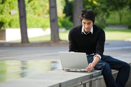 asian laptop: An asian student working on his laptop at the campus