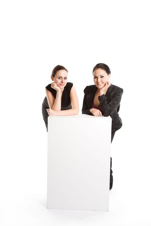 An isolated shot of two businesswomen with a blank billboard photo