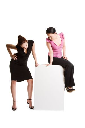 An isolated shot of two businesswomen looking at a blank billboard photo