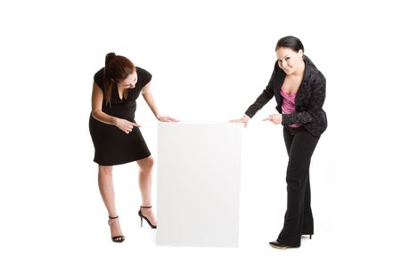 An isolated shot of two businesswomen pointing at a blank billboard photo