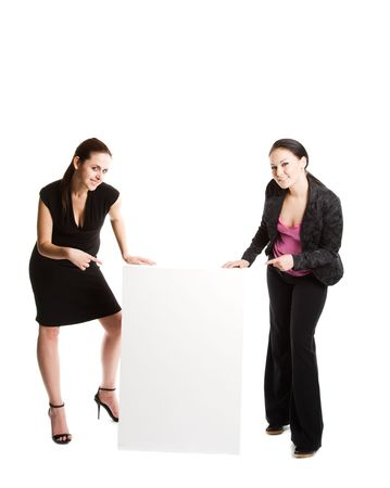 Two businesswomen pointing at a blank billboard photo
