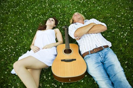 A happy caucasian couple lying down on the grass at a park photo