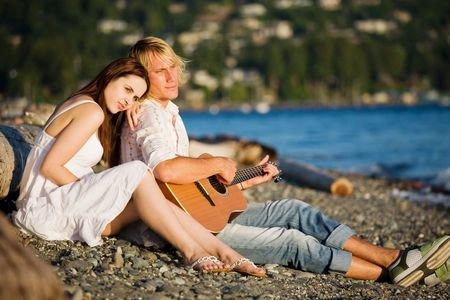 A caucasian couple sitting on the beach playing guitar photo