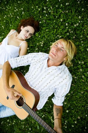 A happy caucasian couple playing guitar at a park photo