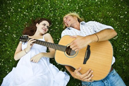 serenata: Una pareja feliz caucasian tocar la guitarra en un parque  Foto de archivo