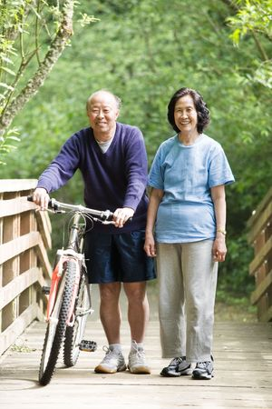 A couple asian mature talking while walking and exercising at a park photo