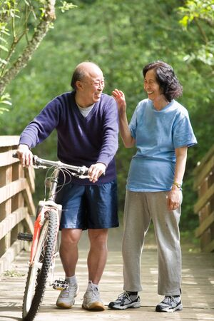 senior female: A couple senior asian talking while walking and exercising at a park Stock Photo