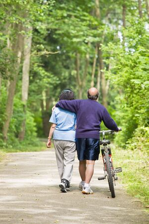 asian sport: A couple senior asian talking while walking and exercising at a park Stock Photo