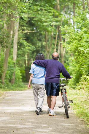 A couple senior asian talking while walking and exercising at a park Reklamní fotografie