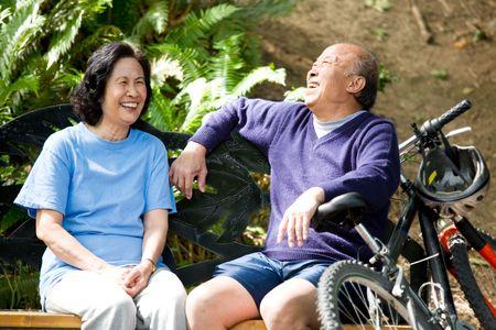 Een schot van hoge asian paar zittend op een bankje in een park