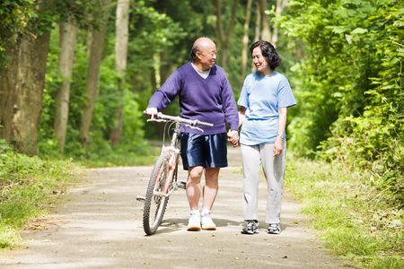 A couple senior asian talking while walking and exercising at a park photo