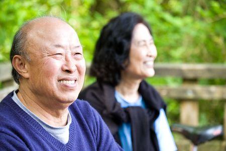 mujeres mayores: Una foto de un par de felices asian superiores al aire libre