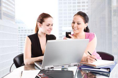 businesspartners: Dos empresarias leer un mensaje de texto durante una reuni�n en la oficina