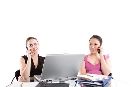 Two businesswomen talking on the phone during a meeting at the office photo