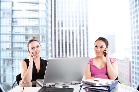 Two businesswomen talking on the phone during a business meeting at the office photo