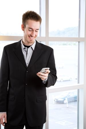 A happy caucasian businessman receiving a text message photo